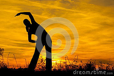 Silhouette of the slim girl stretching out