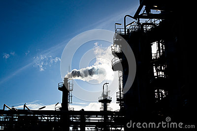 Silhouette of smokestack in petrochemical plant