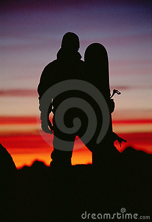 Silhouette of  snowboarder against sunset