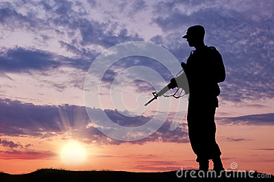 Silhouette of soldier with a gun Stock Photo