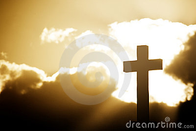 Silhouette of a stone cross in rays of sunlight