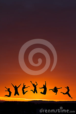 Silhouette of teenagers jumping in sunset