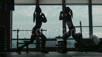 Silhouette of two attractive women doing squats fitness exercise in a gym. Two womans does squats and jumps exercise, wide movement shooting stock video footage