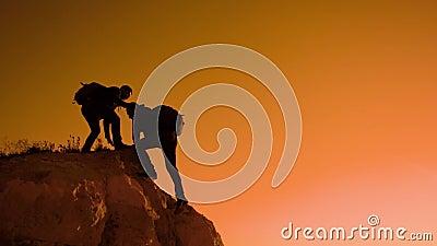 Silhouette two men teamwork tourists climber climbs a mountain. walking tourist hiking adventure climbers sunset climb. Silhouette two men teamwork tourists stock footage