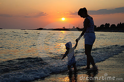 Silhouette of woman and baby on sunset