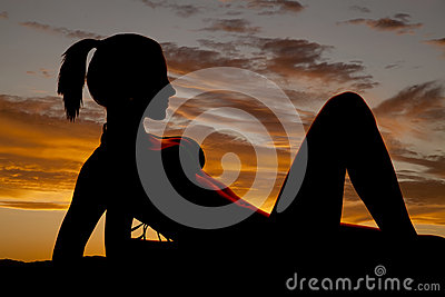 Silhouette of a woman in a bikini on elbows let up