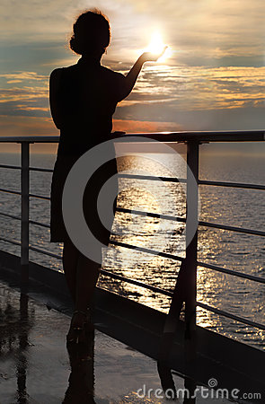 Silhouette of woman holding sun, standing on deck