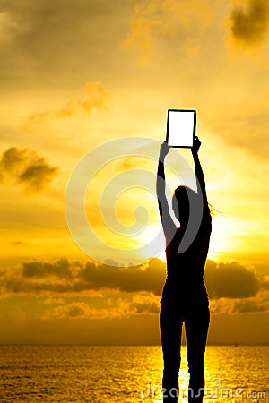 Silhouette of woman holding tablet computer at sunset