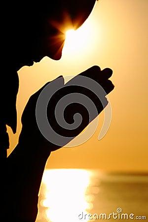 Silhouette of woman prays