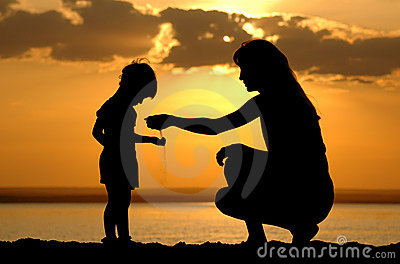 Silhouette of the women to pour sand in hand child
