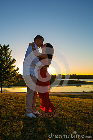 Silhouette of Young Couple Kiss Sunset