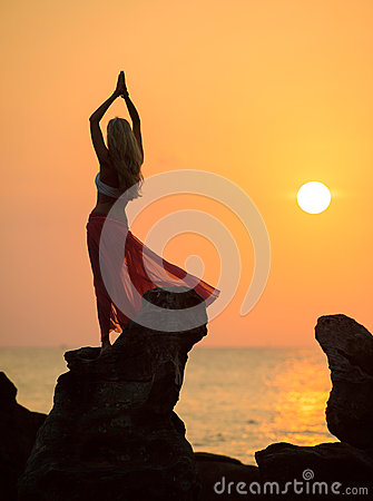 A silhouette of a young girl on rock at sunset 2