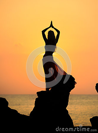 A silhouette of a young girl on rock at sunset 4