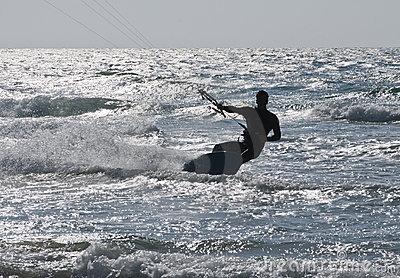 Silhouette of Young Man Kite Boarding in sea Waves