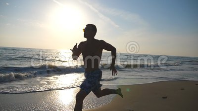 Silhouette of young sporty man running fast along coast during sunrise. Athletic boy training on sea beach. Male. Sportsman exercising outdoor. Healthy active stock video