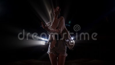 Silhouette of young woman dancing in car lights stock footage