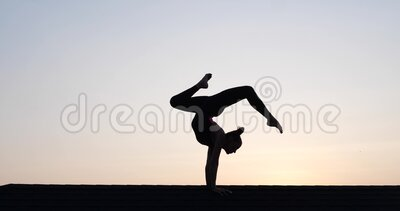 Silhouette of young woman doing acrobatics on the roof over sunset sky background in summer evening stock video