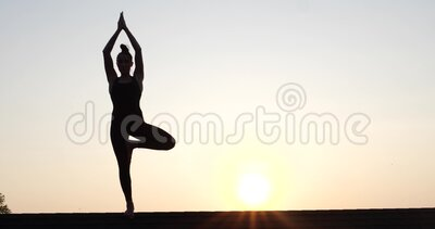 Silhouette of young woman doing acrobatics on the roof over sunset sky background in summer evening stock footage