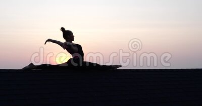 Silhouette of young woman doing split on the roof over sunset sky background in summer evening stock footage