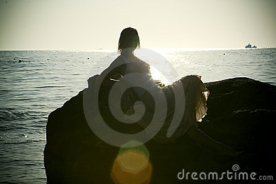 Silhouette of young woman in sea on sunset
