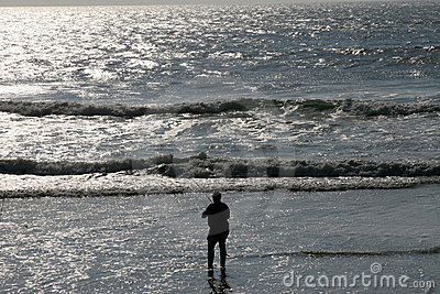 Silhouetted angler on beach
