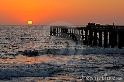 Silhouetted coastal pier