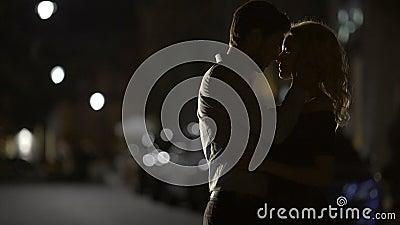 Silhouetten van het houden van van paar die elkaar in de straat omhelzen, verhouding stock videobeelden