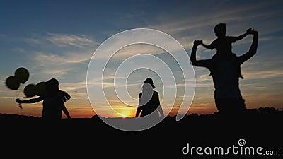 Silhouettes familie die tijdens de zonsondergang in de weide lopen stock video