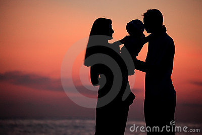 Silhouettes of family on hands against sea decline