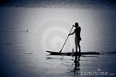 Silhouettes of man canoeing in calm water