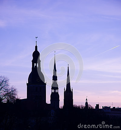 The silhouettes of old riga towers against morning sky