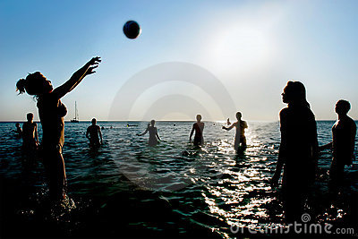 Silhouettes of people playing volleyball in water