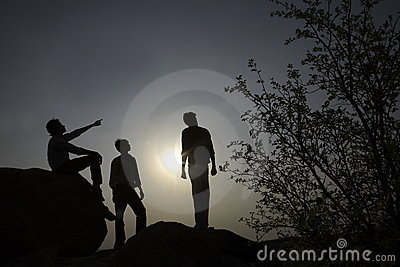 Silhouettes of people on rocks