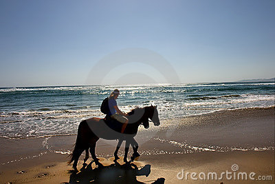 Silhouettes of two horse riders on beach