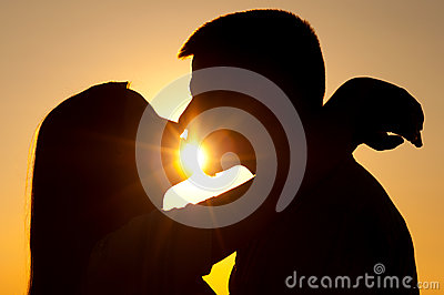 Silhouettes of young couple kissing