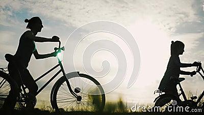 Silhueta da família Biker, pais com dois filhos de bicicleta no pôr do sol Conceito de família amigável vídeos de arquivo