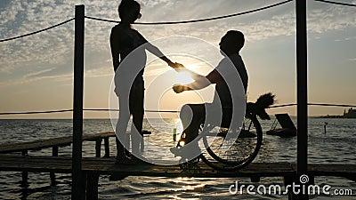 Silhueta de pares loving com a pessoa deficiente na frente marítima perto da água brilhante em feixes brilhantes video estoque