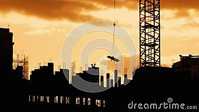 A silhueta do funcionamento do guindaste no canteiro de obras eleva o peso das constru??es de a?o vídeos de arquivo