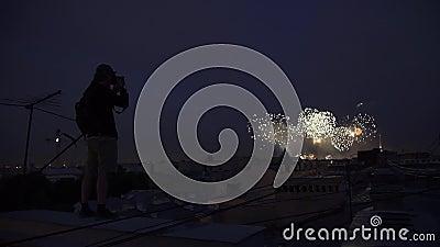 Silhueta do homem novo que está no telhado da construção que toma a foto dos fogos-de-artifício vídeos de arquivo