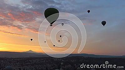Silhueta dos balões de ar quente que voam sobre Cappadocia no nascer do sol video estoque