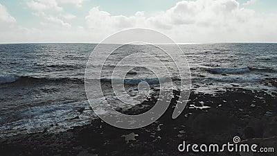 Silhueta escura da pessoa fêmea com os braços largamente abertos no ar que está no penhasco com as ondas fortes que batem a praia vídeos de arquivo