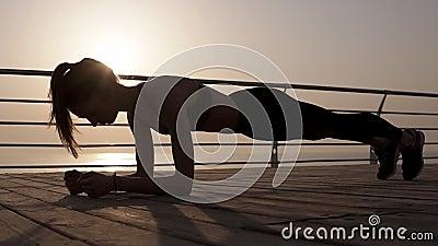 Silhueta fêmea nova que faz o exercício da prancha em um beira-mar Corpo forte dusk Manhã azul video estoque