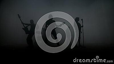 Silhuetas do grupo de rock que executam o concerto de rocha na fase Faixa da música rock video estoque