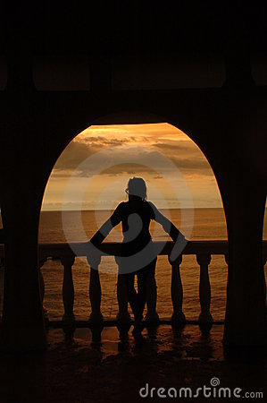 Silhuette of a women in an arch against a beautiful tropical sunset