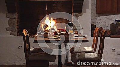 Sillas y tabla cerca de la chimenea, preparación deliciosa de la comida, espera para los pares de los amantes, cena romántica, co