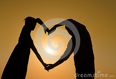 Sillhouette loving couple at sunset with heart