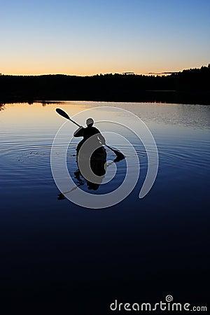 Sillouette of man kayaking on lake