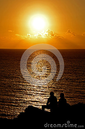 Silohuetted People over a Sunset in the Atlantic Ocean