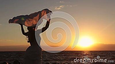 Silueta de la mujer con la bufanda en la playa en la puesta del sol almacen de metraje de vídeo