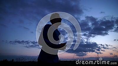 Silueta de un hombre que corre en el camino en la puesta del sol almacen de metraje de vídeo